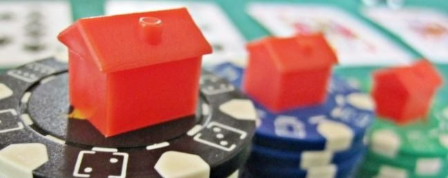 Are you gambling on the housing market? This image contains three monopoly homes on a stack of casino chips with some playing cards in the background.