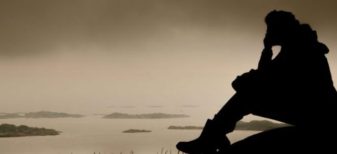 person sits on the edge of a body of water, seemingly deep into his or her thoughts