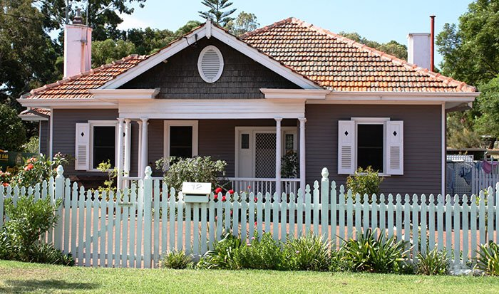 Suburban house with a white picket fence. Would you buy it outright or rent to own?