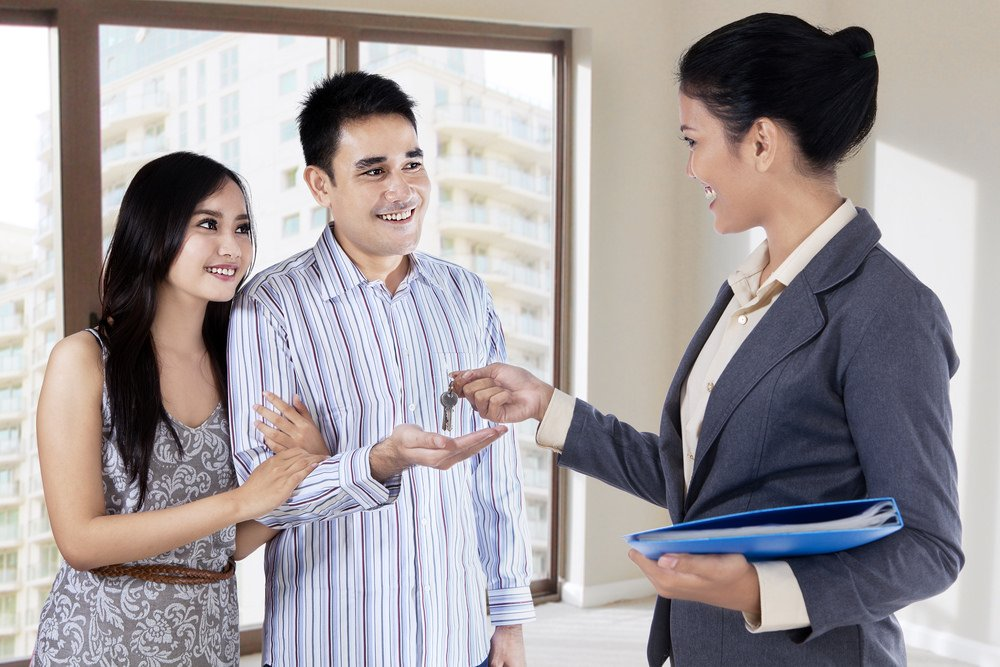 Real estate agent hands clients the keys to a home.